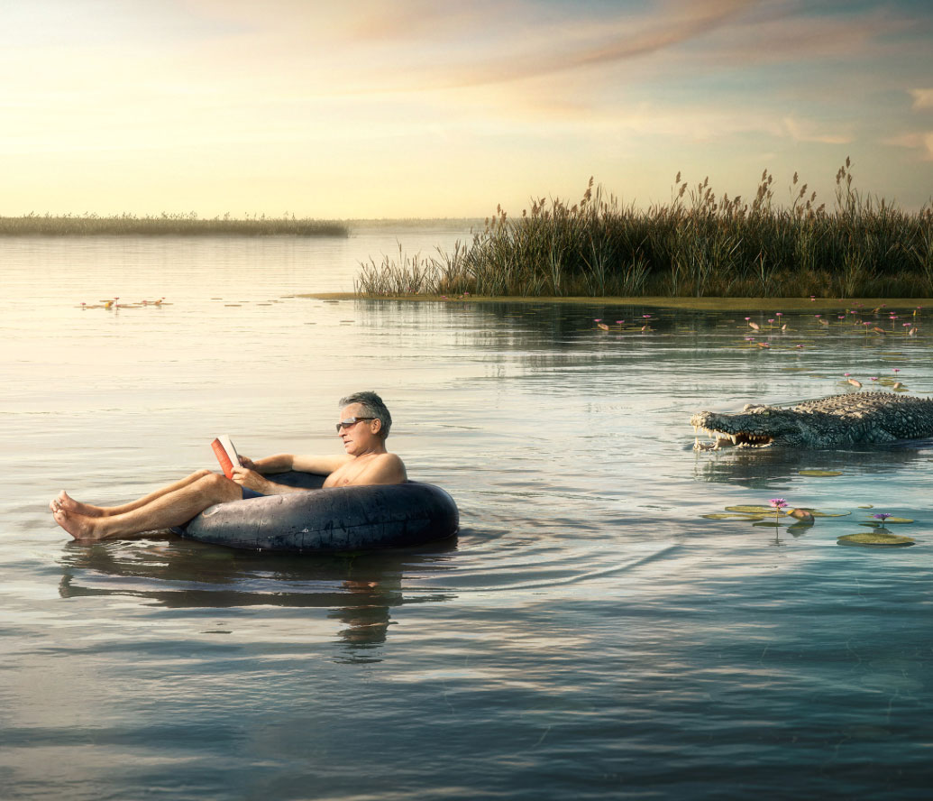 Jesse Zamjahn Pixteur 3D CGI of man floating in a inner tube unaware of the alligator swing in his direction.